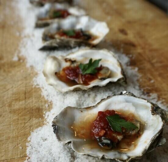 oesters om te grillenZijn oesters die op zout liggen met tomaat knoflook en peterselie. Liggend op een rijtje