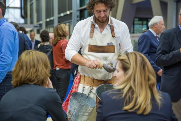 Oesterman Gijs opent oesters op een beurs