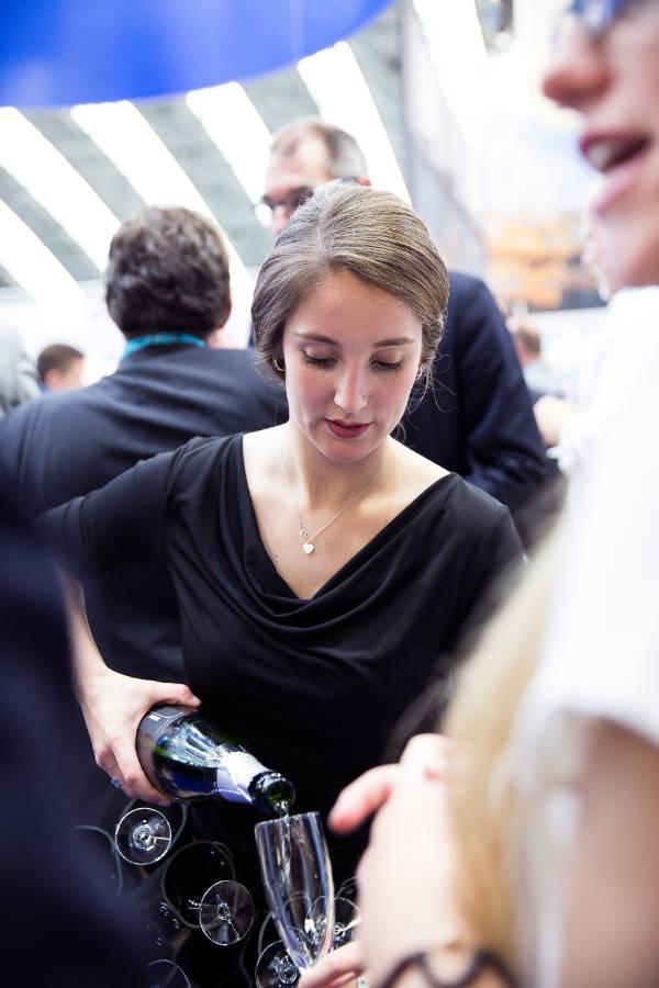 Champagne meisje van Oestercompagnie schenkt champagne in