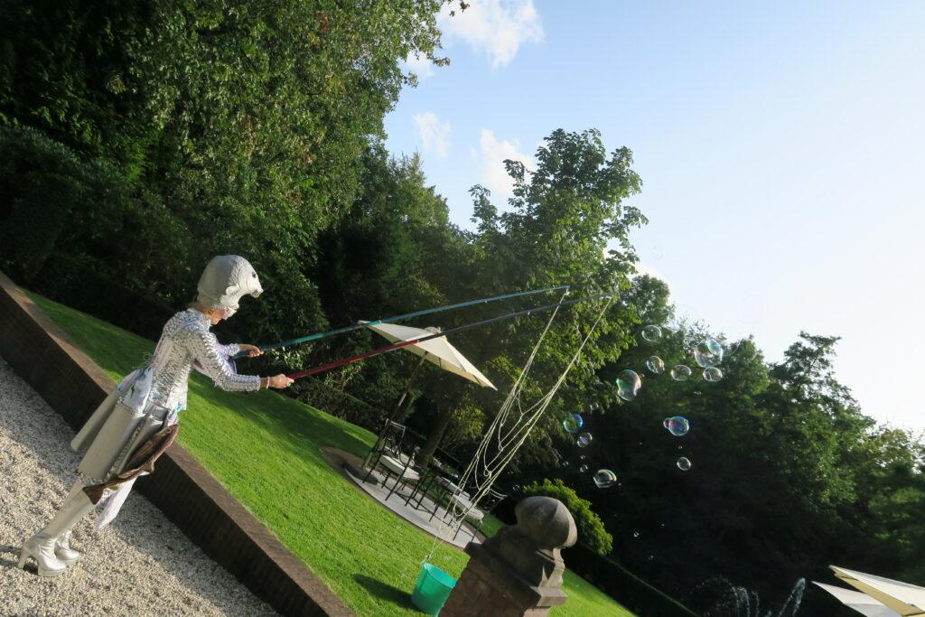 Oestercompagnie is bij viering 10 jarig bestaan Vision. Vrouw als vis verkleed staat in de tuin met een groot visnet met bellenblaas