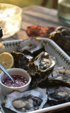 Een bord met oesters, sjalotjes en citroenen